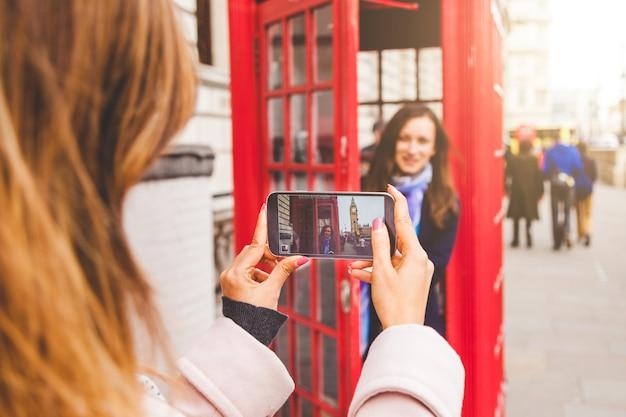Freunde, die ein foto in einer london-telefonzelle machen