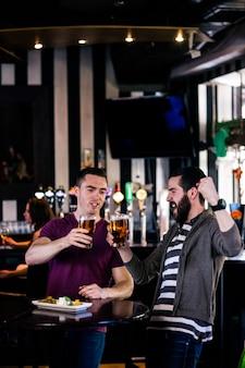Freunde, die ein halbes liter haben und in einer bar zujubeln