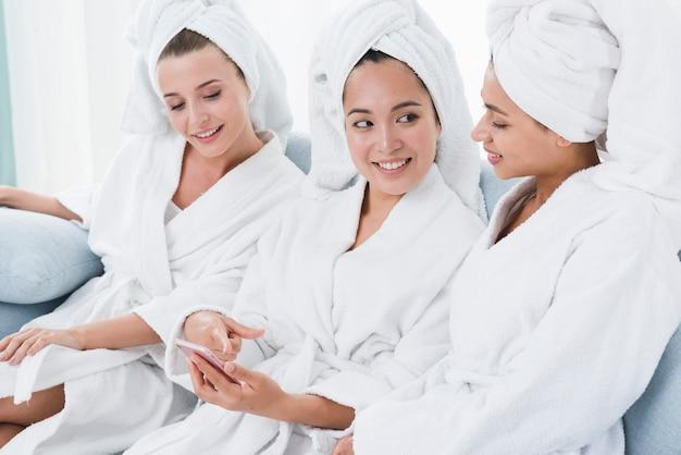 Freunde, die ein mobile in einem badekurort verwenden