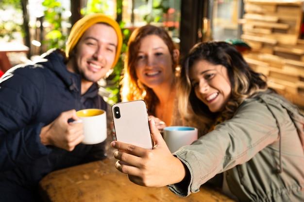 Freunde, die ein selfie an der kaffeestube nehmen