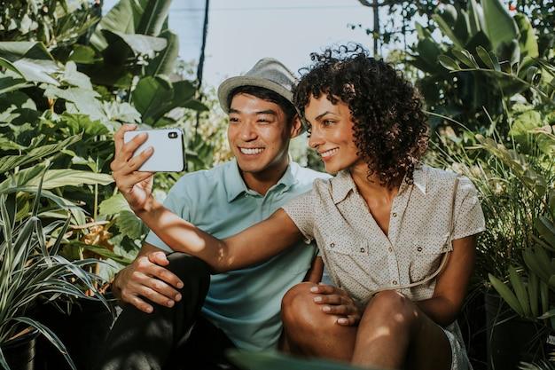 Freunde, die ein selfie an einem garten nehmen