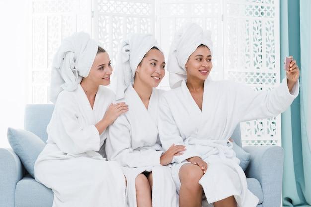 Freunde, die ein selfie in einem badekurort nehmen