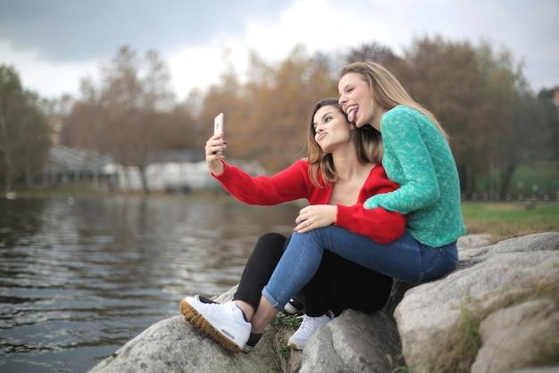 Freunde, die ein selfie machen und neben dem see sitzen
