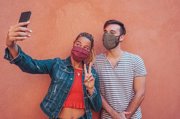Freunde, die ein selfie mit gesichtsmaske in coronavirus-zeit zum schutz nehmen