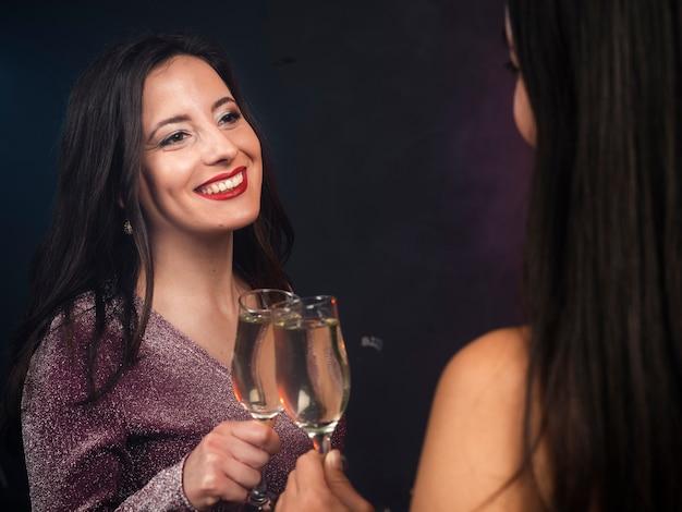Freunde, die einander mit champagner an der party der neuen jahre betrachten