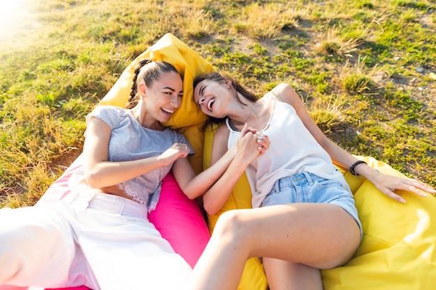 Freunde, die eine spaßzeit haben, auf sitzsäcken zu sitzen