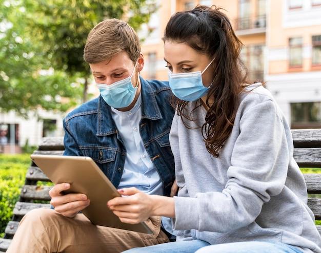 Freunde, die eine tablette betrachten, während sie medizinische masken tragen