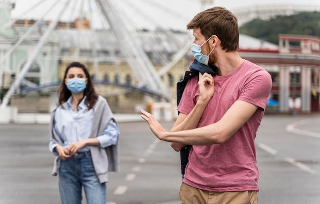 Freunde, die einen spaziergang machen, während sie medizinische masken tragen