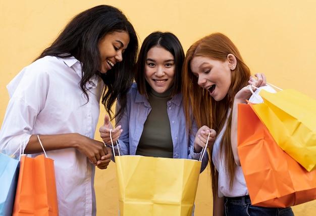 Freunde, die einkaufstaschen im freien halten