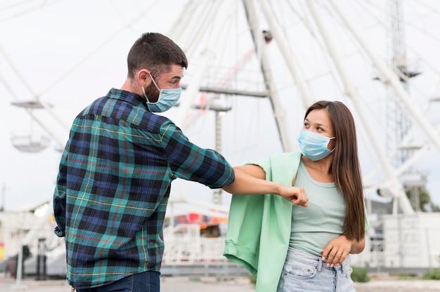 Freunde, die ellbogengruß verwenden, während sie medizinische masken tragen