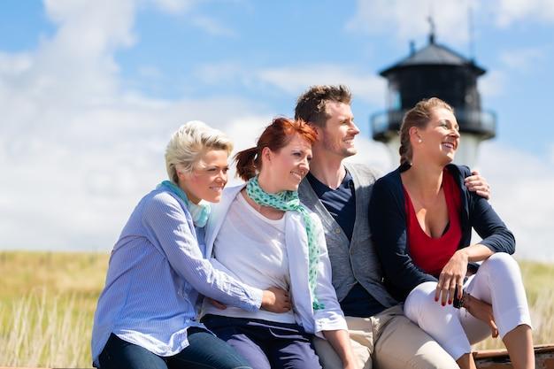 Freunde, die flaschenbier trinken, genießen urlaub am deutschen nordseestrand