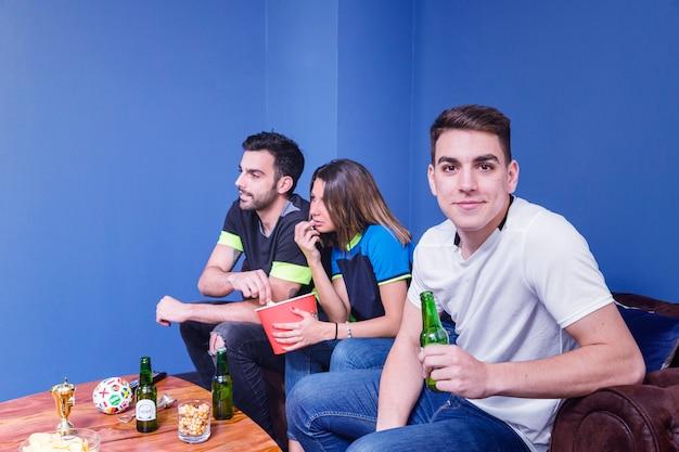 Freunde, die fußball auf couch aufpassen