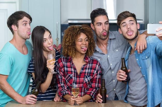 Freunde, die gesichter beim nehmen von selfie in der küche machen
