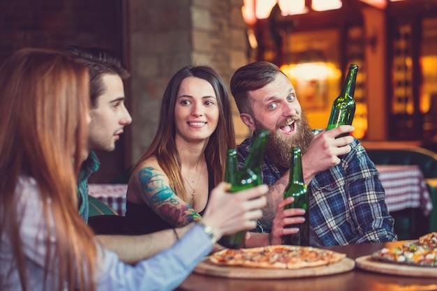 Freunde, die getränke haben und pizza in einer bar essen