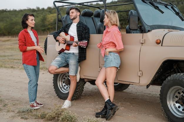 Freunde, die gitarre spielen, während sie mit dem auto reisen
