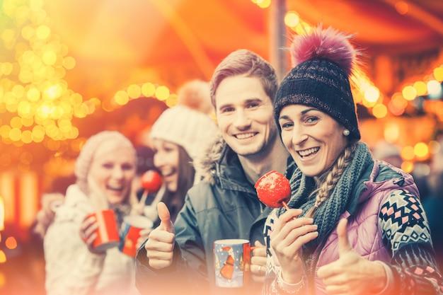 Freunde, die glühwein auf weihnachtsmarkt trinken