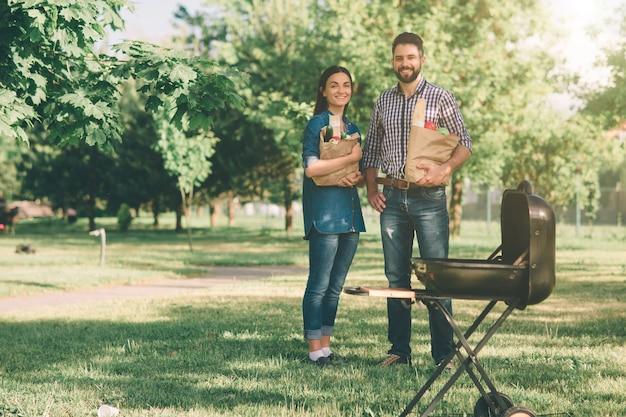 Freunde, die grillen machen und in der natur zu mittag essen. paare, die spaß beim essen und trinken bei einem picknick haben - fröhliche leute auf der grillparty