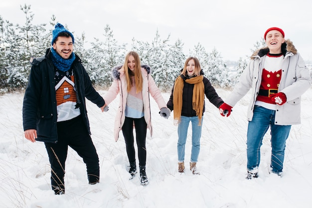 Freunde, die hände im winterwald anhalten
