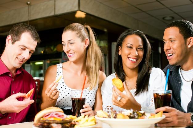 Freunde, die hamburger essen und soda trinken