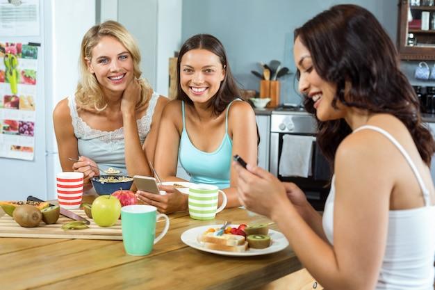 Freunde, die handys beim zu hause frühstücken verwenden