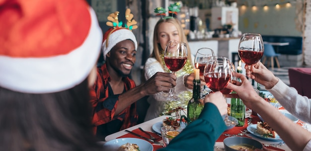 Freunde, die heiligabend-klirrgläser feiern, sitzen am tisch.