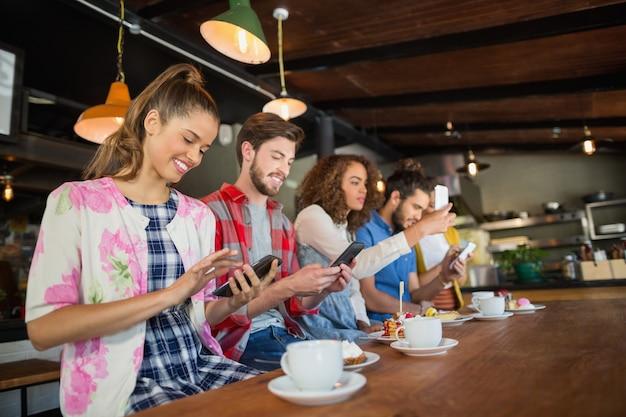 Freunde, die ihre handys im restaurant benutzen