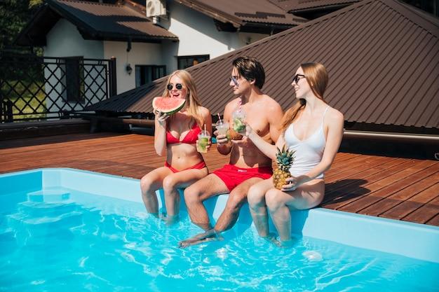 Freunde, die ihren urlaub am pool genießen