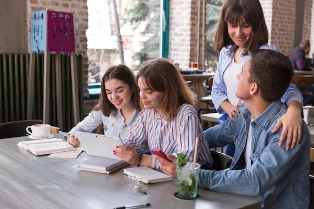 Freunde, die im café mit tablette sitzen