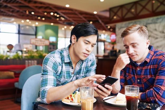 Freunde, die im café zu mittag essen und die dating-app auf dem smartphone durchlaufen, wischen nach links oder rechts