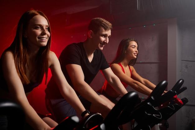 Freunde, die im dunklen neonbeleuchteten fitnessstudio trainieren und trainieren, fahren zusammen fahrrad und lächeln