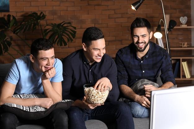 Freunde, die im fernsehen comedy schauen und zu hause popcorn essen