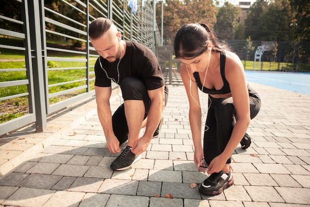 Freunde, die im freien trainieren, binden ihre schnürsenkel