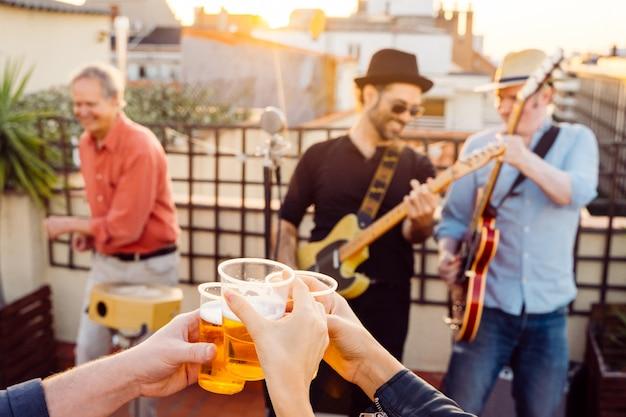Freunde, die im sommer bei einem live-konzert auf einem dach einen toast machen. junge leute, die tassen lagerbier halten und jubeln. freizeit- und musikkonzept. glückliche leute, die spaß beim biertrinken haben.