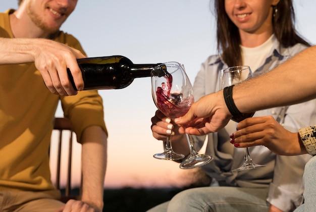 Freunde, die in der abenddämmerung im freien wein trinken