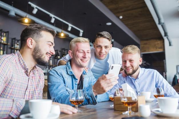 Freunde, die in der bar mit den getränken betrachten handy sitzen