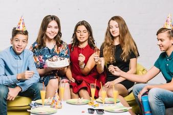Freunde, die in der Hand die Feuercracker sitzen mit dem Geburtstagsmädchen halten Kuchen in der Hand halten