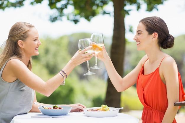 Freunde, die in einem restaurant ein glas wein rösten