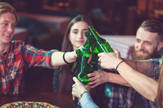 Freunde, die in einer bar etwas trinken, sitzen an einem holztisch mit bier und pizza.