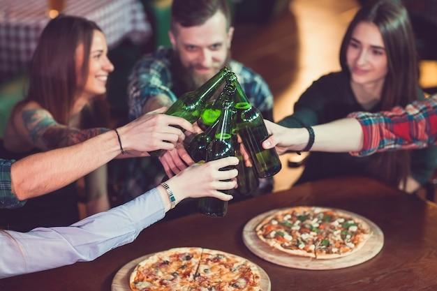 Freunde, die in einer bar etwas trinken, sitzen an einem holztisch mit bieren und pizza.