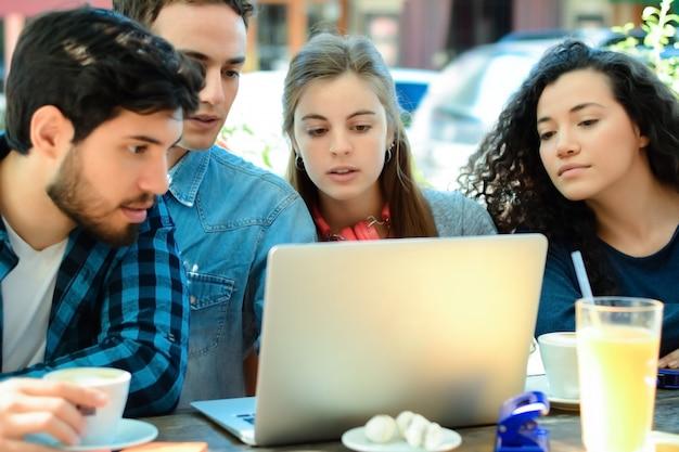 Freunde, die in einer kaffeestube mit einem laptop sich treffen.