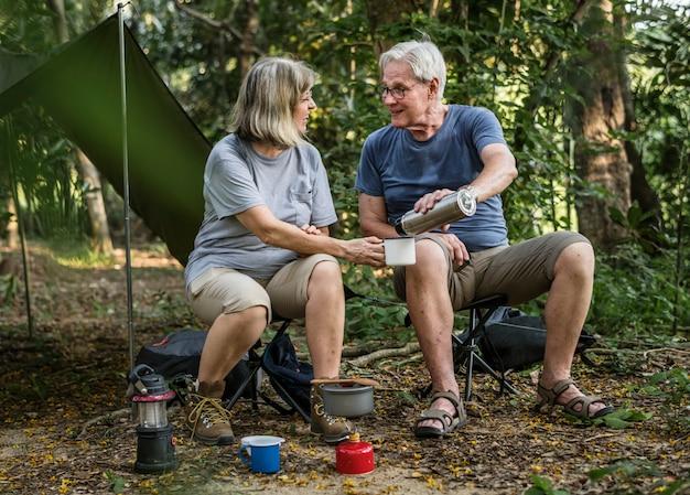 Freunde, die kaffee auf einem campingplatz trinken