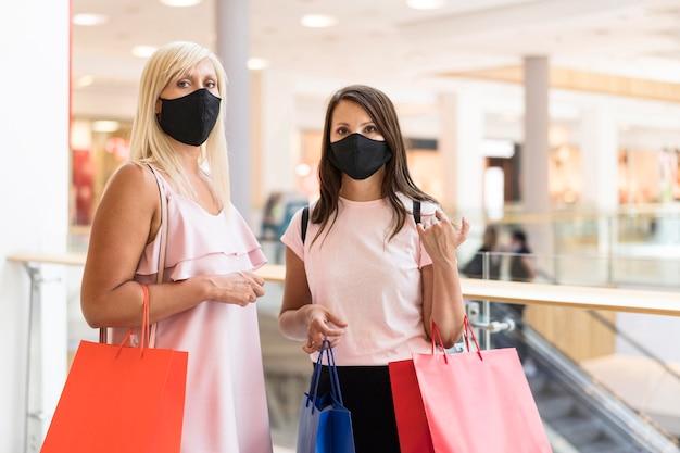 Freunde, die masken im einkaufszentrum tragen und einkaufstaschen halten