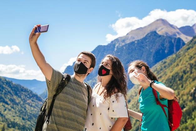 Freunde, die masken tragen und ein selfie machen