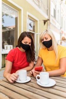 Freunde, die masken tragen und einen kaffee genießen