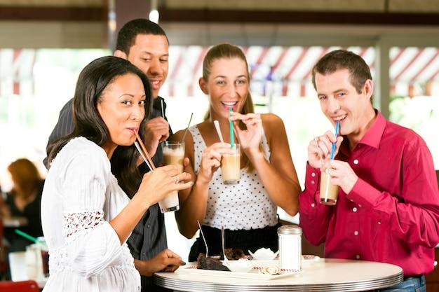 Freunde, die milchkaffee trinken und kuchen essen