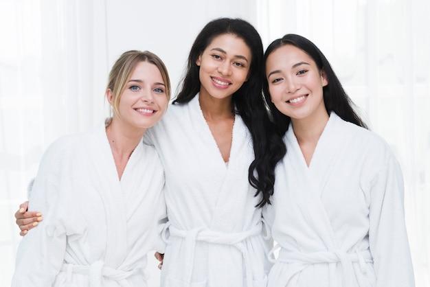 Freunde, die mit bademantel in einem badekurort aufwerfen