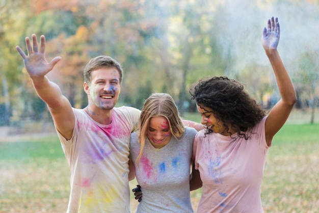 Freunde, die mit farbiger farbe am holi spielen