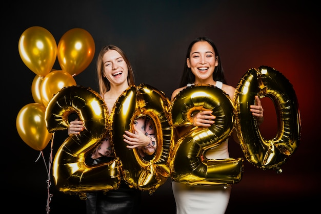 Freunde, die mit goldenen ballonen an der party der neuen jahre aufwerfen