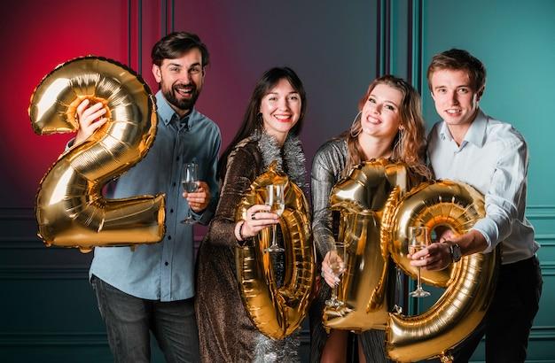 Freunde, die mit goldenen zahlballonen aufwerfen