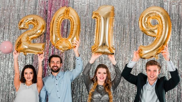 Freunde, die mit goldener party des neuen jahres der ballone aufwerfen